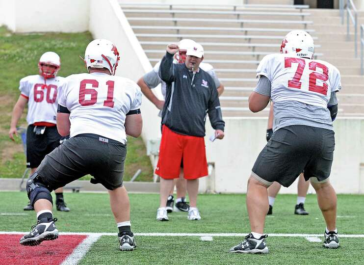 The Lamar University offensive lineman work on drills with Director of Football Operations Chuck Lan