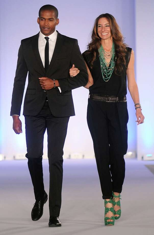 Honoree Lisa Holthouse is escorted down the runway at the annual Houston Chronicle's Best Dressed Luncheon at the Westin Galleria Hotel Tuesday April 3, 2013.(Dave Rossman photo) Photo: Dave Rossman, For The Houston Chronicle / © 2013 Dave Rossman