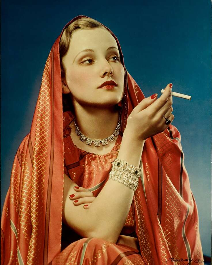 1936:  A color advertisement for Lucky Strike cigarettes showing a young woman dressed in red, smoking a cigarette held in her right hand. Photo: Nickolas Muray, Getty Images / Hulton Archive