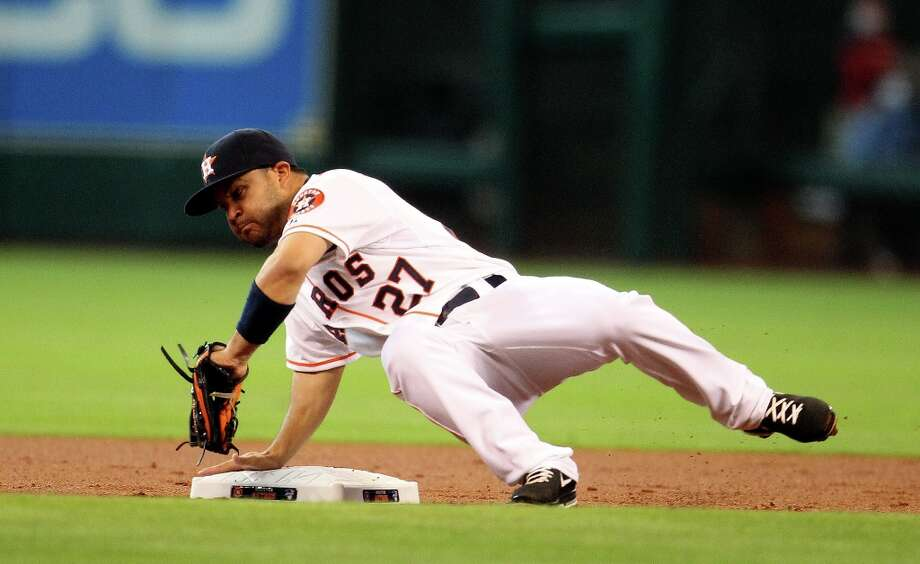 Astros second baseman Jose Altuve dives for a ball as Rangers first baseman Lance Berkman attempted to steal second base during the first inning. Photo: Karen Warren / © 2013 Houston Chronicle