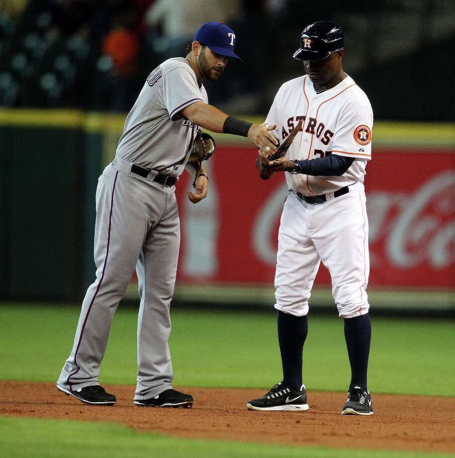 Mitch Moreland hands pieces of bat to Astros first base coach Dave Clark after Brett Wallace broke a bat grounding out during the first inning. Photo: Karen Warren / © 2013 Houston Chronicle