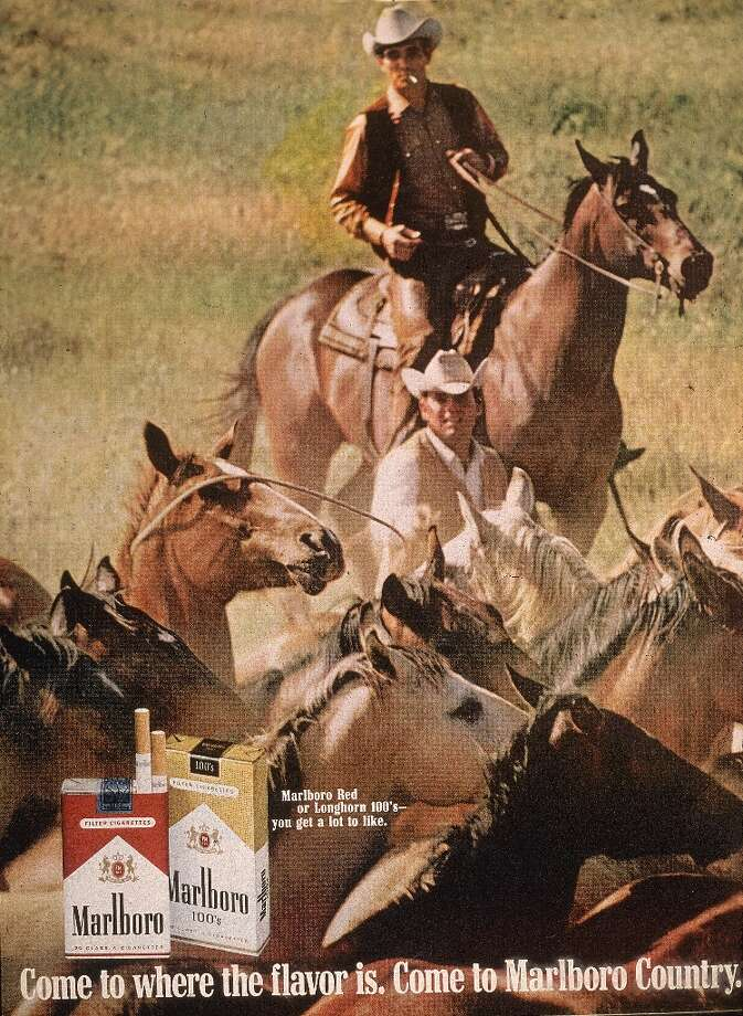 Image of two 'Marlboro Man' cowboys herding horses in a magazine ad for Marlboro cigarettes, 1970s. Photo: Blank Archives, Getty Images / 2006 Getty Images
