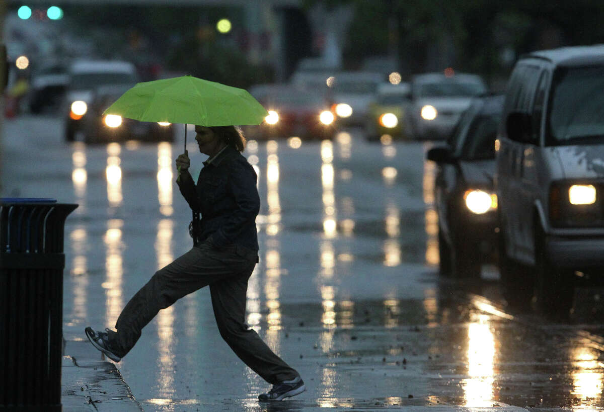 A pedestrian crosses a rain slickened section of East Commerce Street near Rivercenter Mall Wednesday April 3, 2012 after storms moved through San Antonio and the Hill Country.