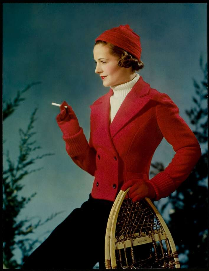 1936:  A seasonal advertisement for Lucky Strike cigarettes showing a young woman dressed in winter gear smoking a cigarette in her right hand, She holds a pair of snowshoes in her left hand. Photo: Nickolas Muray, Getty Images / Hulton Archive