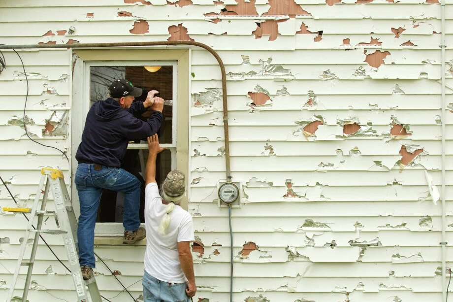 Keith Dressman, left, and his brother, Kim, replace a broken window following a hail storm, that also damaged the home's siding, Wednesday, April 3, 2013, in Hitchcock. Photo: Brett Coomer, Houston Chronicle / © 2013 Houston Chronicle