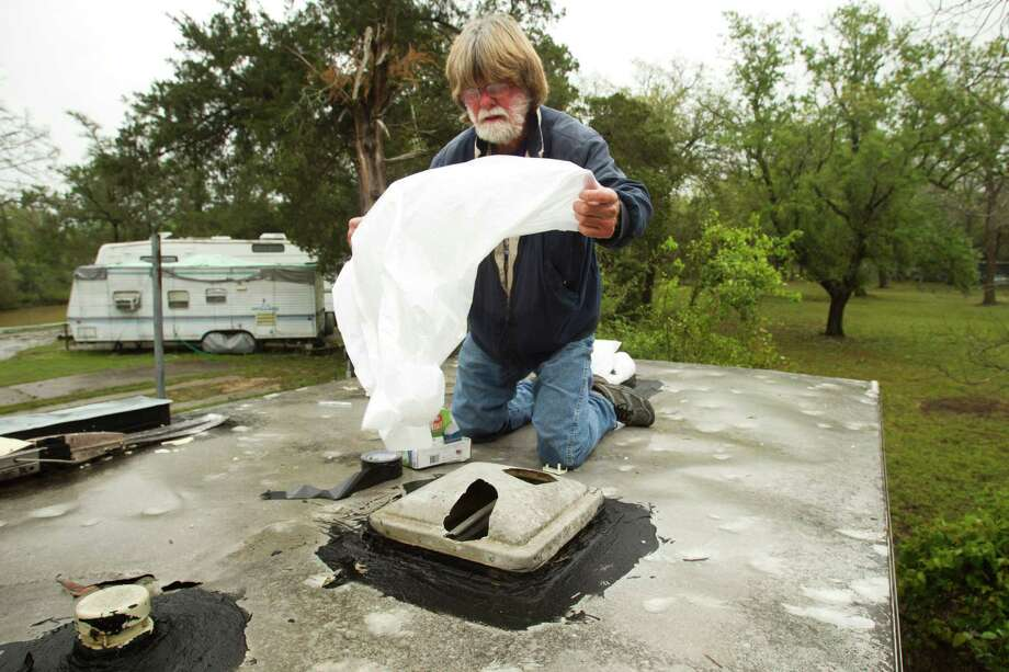 John Williams opens a plastic bag to cover up holes in a skylight of his trailer following a hail storm Wednesday, April 3, 2013, in Hitchcock. Photo: Brett Coomer, Houston Chronicle / © 2013 Houston Chronicle