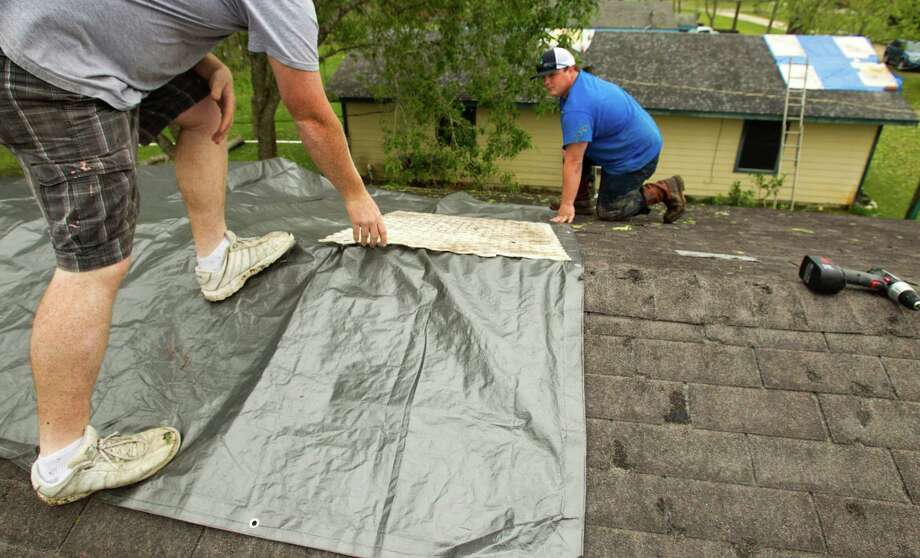 Steven Beall, left, and Blake Jackson cover a damaged roof with a tarp following a hail storm Wednesday, April 3, 2013, in Santa Fe. Photo: Brett Coomer, Houston Chronicle / © 2013 Houston Chronicle