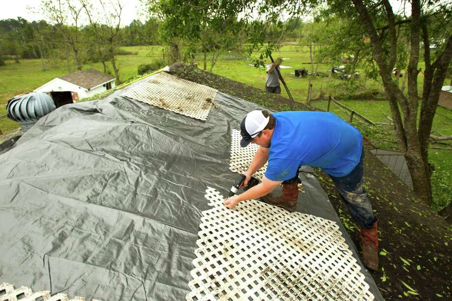 Blake Jackson covers a damaged roof with a tarp following a hail storm Wednesday, April 3, 2013, in Santa Fe. Photo: Brett Coomer, Houston Chronicle / © 2013 Houston Chronicle