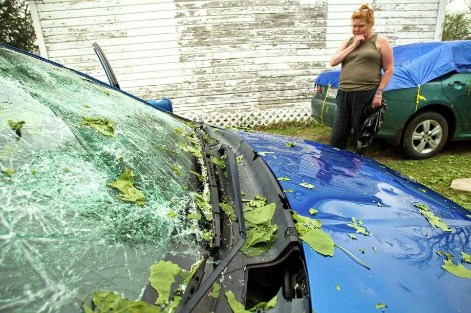 Derinda Norred walks past her damaged car following a hail storm Wednesday, April 3, 2013, in Santa Fe. Photo: Brett Coomer, Houston Chronicle / © 2013 Houston Chronicle