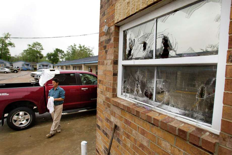 Jimmy Singh walks past a damaged window at the Bostonian Inn & Suites following a hail storm Wednesday, April 3, 2013, in Hitchcock. Photo: Brett Coomer, Houston Chronicle / © 2013 Houston Chronicle