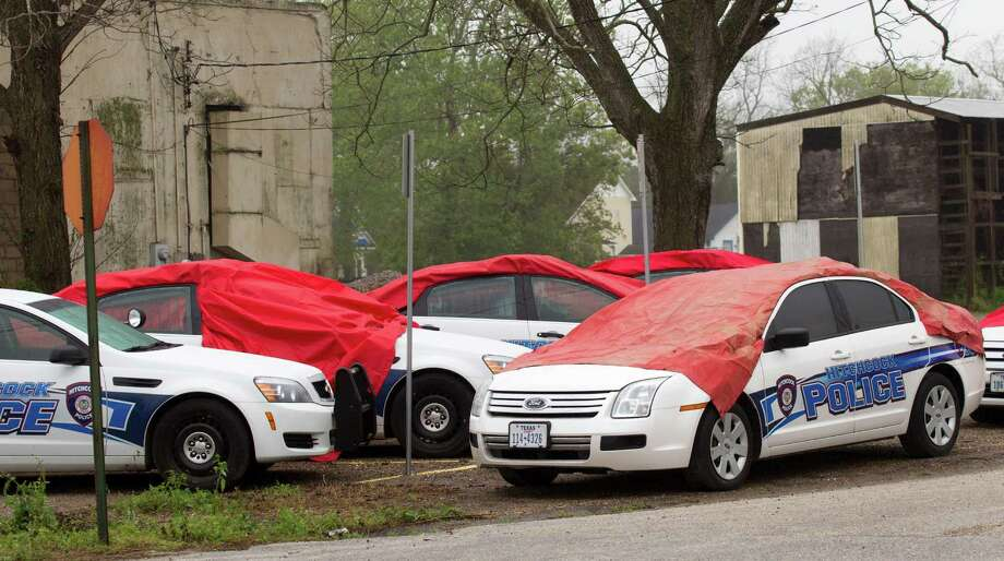Several Hitchcock Police cars sit under tarps after they were damaged by a hail storm Wednesday, April 3, 2013, in Hitchcock. Photo: Brett Coomer, Houston Chronicle / © 2013 Houston Chronicle