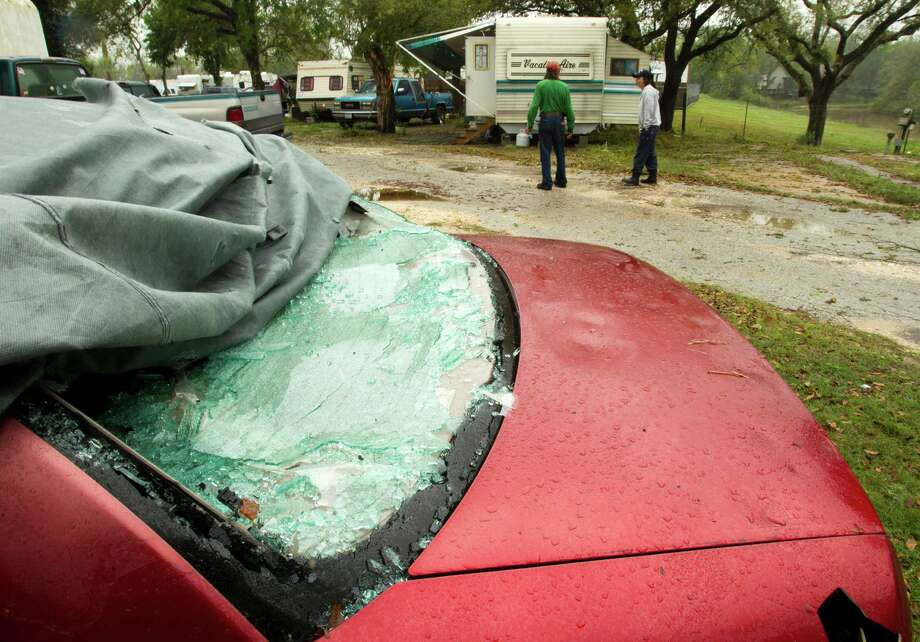 A car sits with its back windshield broken out and several dents following a hail storm Wednesday, April 3, 2013, in Hitchcock. Photo: Brett Coomer, Houston Chronicle / © 2013 Houston Chronicle