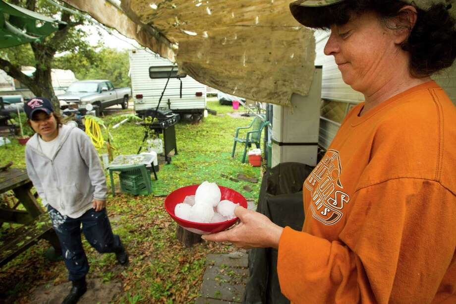 Jeanne Malone, left, walks past Christine Hubbard as she holds a bowl full of hail stones she collected following a hail storm Wednesday, April 3, 2013, in Hitchcock. Photo: Brett Coomer, Houston Chronicle / © 2013 Houston Chronicle