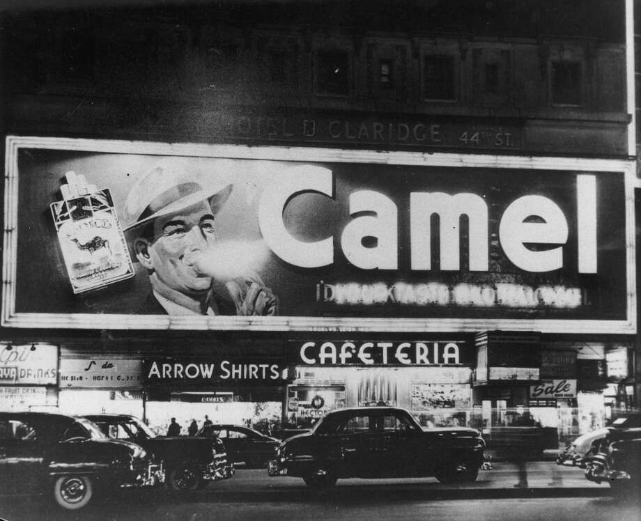 A neon billboard for Camel cigarettes sits above a cafeteria and assorted storefronts in Times Square at night while cars pass, New York City. Photo: Hulton Archive, Getty Images / Archive Photos