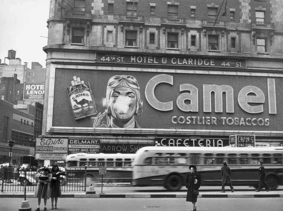 circa 1944:  Street scene showing a Camel cigarette billboard with a pilot's face smoking on the exterior of the Claridge Hotel in Times Square, New York City. Photo: Anthony Potter Collection, Getty Images / Archive Photos
