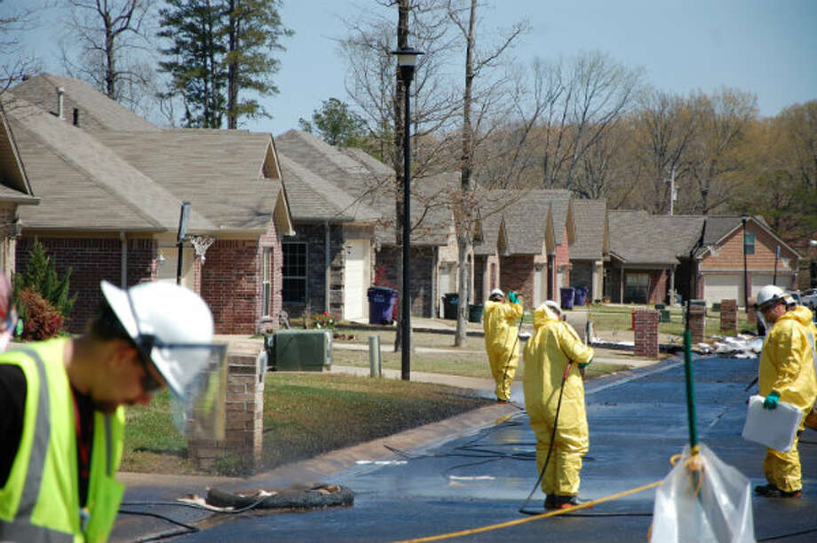 Crews work to clean up oil in Mayflower, Ark., on Monday, April 1, 2013, days after a pipeline ruptured and spewed oil over lawns and roadways. Photo: Jeannie Nuss, AP