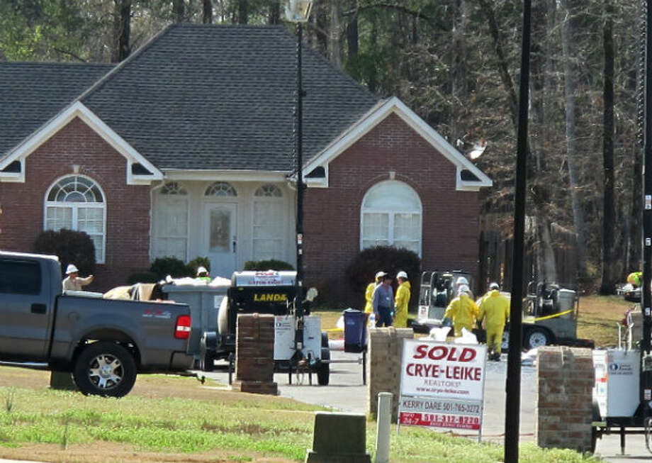 Cleanup crews cover North Starlite Road in Northwoods Subdivision in Mayflower, Ark. Sunday, March 31, 2013. A real estate sign stands clear against some of the cleanup operations. Photo: Alan English, AP Photo/The Log Cabin Democrat