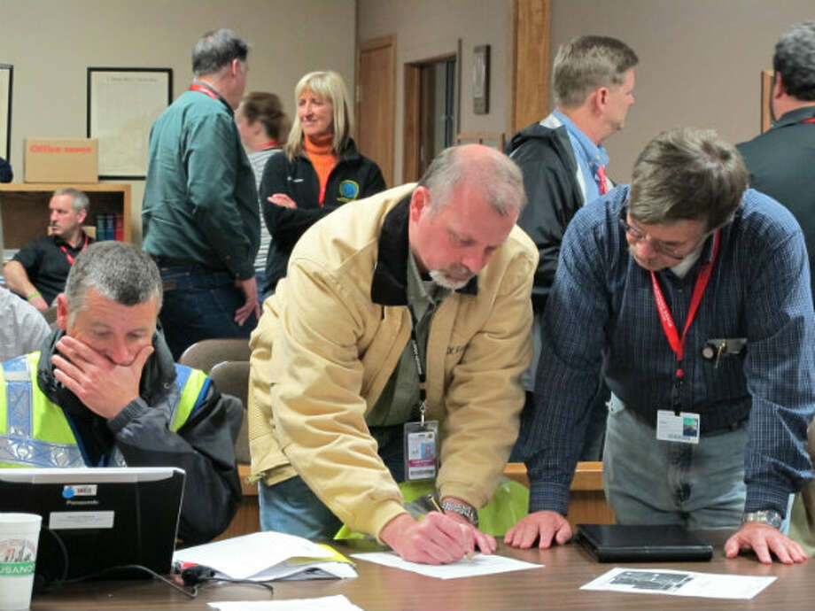 Faulkner County Judge Allen Dodson, center, helps develop plans of action plans as part of incident review at temporary command operations at Mayflower, Ark., City Hall, Sunday, March 31, 2013. Next to him are Nicolas Brescia, left, EPA On Scene Coordinator at USEPA, and Dean Vanderhoff, right, incident commander at ADEQ. Residents affected by an oil spill in central Arkansas could be displaced for weeks, officials said, as crews continued to clean up the thousands of barrels of oil and water that leaked from a pipeline. Photo: Alan English, AP Photo/The Log Cabin Democrat