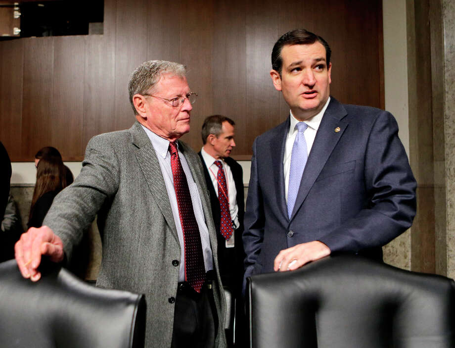 At the Senate Armed Services Committee, Sen. Ted Cruz, R-Texas, right, confers with Sen. James Inhofe, R-Okla., the ranking member, left, during a short recess in the confirmation hearing of Chuck Hagel, a former two-term senator and President Obama's choice to lead the Pentagon, on Capitol Hill in Washington, Thursday, Jan. 31, 2013. Hagel faced strong Republican resistance and was forced to explain past remarks and votes even as he appeared on a path to confirmation as Obama second-term defense secretary and the nation's 24th Pentagon chief.  (AP Photo/J. Scott Applewhite) Photo: J. Scott Applewhite, Associated Press
