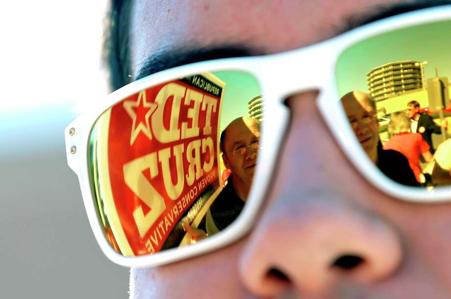 A campaign sign for Republican candidate for U.S. Senate Ted Cruz is reflected in the sunglasses of campaign intern Lorenzo Garcia as he waits for Cruz to arrive outside a polling location Tuesday, Nov. 6, 2012, in Houston. Cruz is running against Democrat Paul Sadler to replace retiring U.S. Sen. Kay Bailey Hutchison. Photo: David J. Phillip, Associated Press