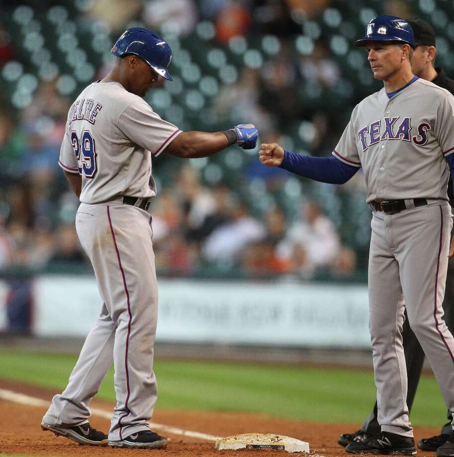 Rangers third baseman Adrian Beltre celebrates his single with first base coach Dave Anderson during the sixth inning. Photo: Karen Warren, Chronicle / © 2013 Houston Chronicle