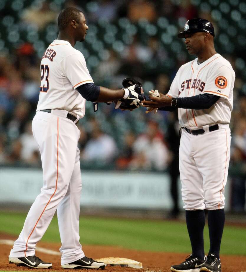 Astros first baseman Chris Carter hands his batting helmet over to first base coach Dave Clark after flying out to end the sixth inning. Photo: Karen Warren, Chronicle / © 2013 Houston Chronicle