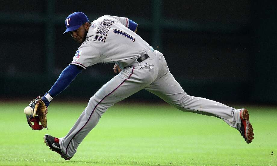 Rangers shortstop Elvis Andrus reaches out for the single hit by Astros center fielder Justin Maxwell during the seventh inning. Photo: Karen Warren, Chronicle / © 2013 Houston Chronicle
