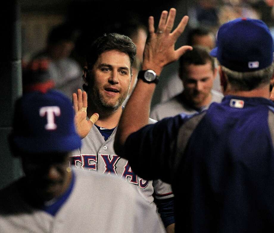 Rangers first baseman Lance Berkman (27) celebrates his RBI double as he returns to the dugout after being replaced by a pinch runner during the eighth inning. Photo: Karen Warren, Chronicle / © 2013 Houston Chronicle