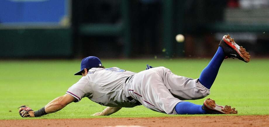 Rangers second baseman Ian Kinsler dives for a ball hit by Astros shortstop Ronny Cedeno during the third inning. Photo: Karen Warren , Chronicle / © 2013 Houston Chronicle