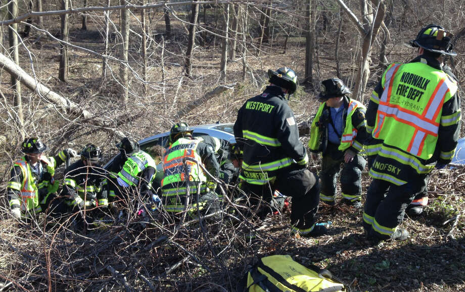 Firefighters from Westport and Norwalk at the scene of a crash Wednesday on the Merritt Parkway, between northbound Exits 40 and 41, where the driver was trapped in the car after it tumbled down an embankment and struck a tree.  WESTPORT NEWS, CT 4/3/13 Photo: Westport Fire Department / Westport News contributed