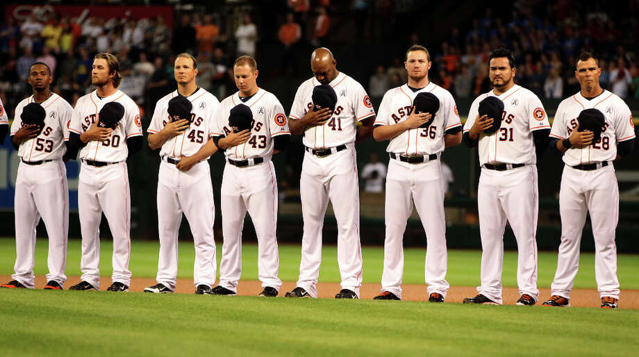Astros players line up as Lyle Lovett sings the National Anthem. Photo: Karen Warren, Houston Chronicle / © 2013 Houston Chronicle
