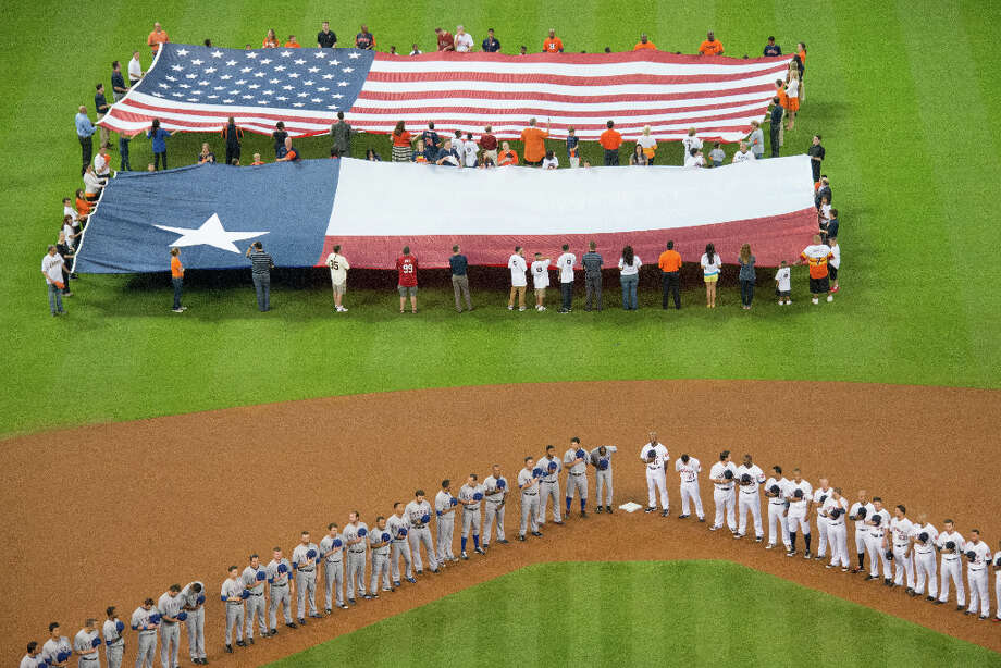 The U.S. and Texas flags are displayed in centerfield as the Astros and Rangers observe a moment of silence for the victims of the Sandy Hook shooting before the season opener. Photo: Smiley N. Pool, Houston Chronicle / © 2013  Smiley N. Pool