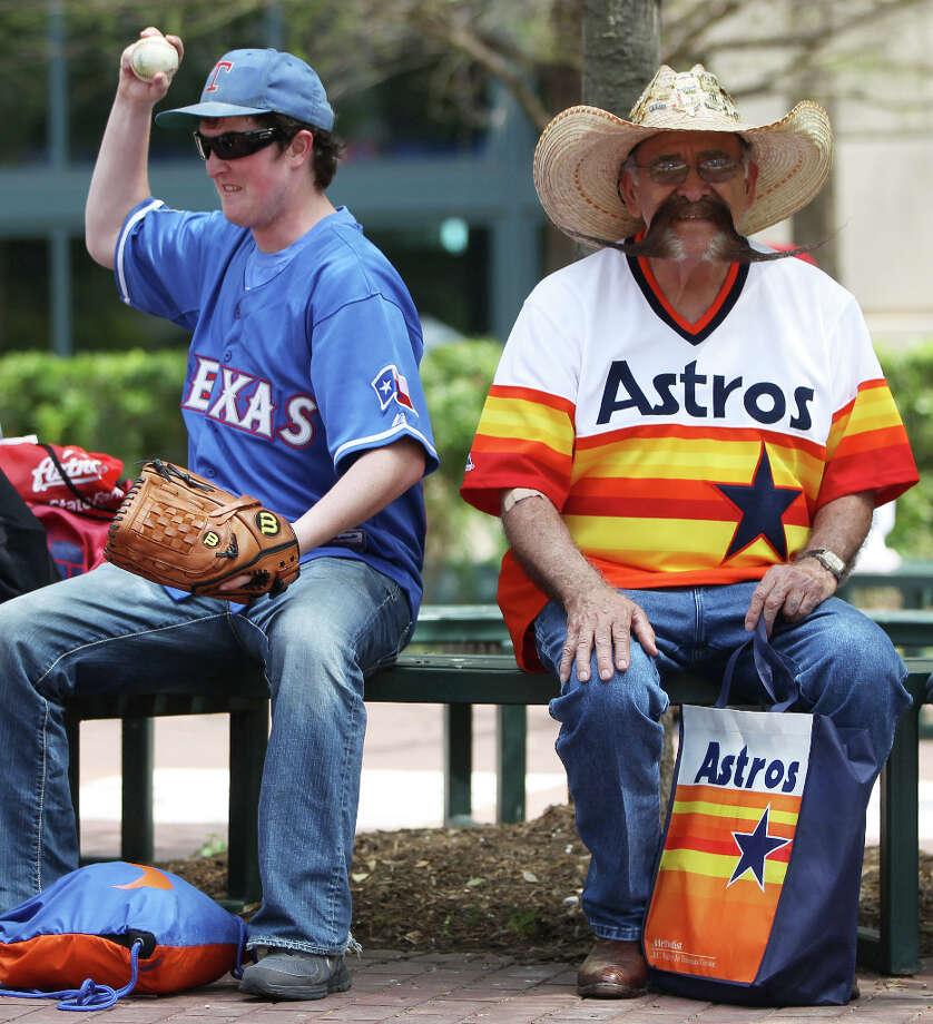 Tony Genna, left, a Texas Ranger fan sits next Valentin Jalomo, an Astros fan, right, during the street festival. Photo: Karen Warren, Houston Chronicle / © 2013 Houston Chronicle