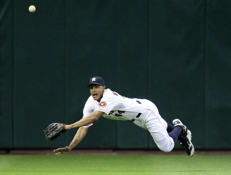 Astros center fielder Justin Maxwell dives for the out on Texas Rangers shortstop Elvis Andrus during the third inning. Photo: Karen Warren, Houston Chronicle / © 2013 Houston Chronicle