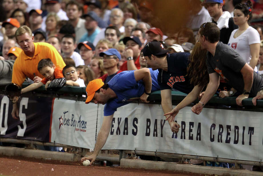Fans pick up a foul ball along the first base side during the third inning. Photo: Karen Warren, Houston Chronicle / © 2013 Houston Chronicle