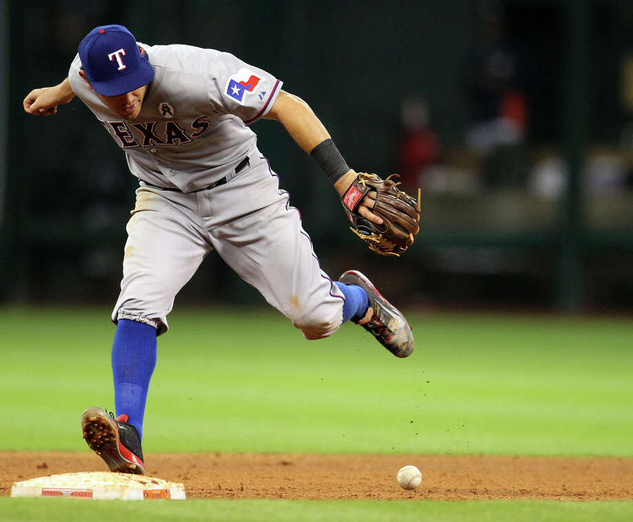 Rangers second baseman Ian Kinsler bobbles a ground hit by Astros third baseman Matt Dominguez during the eighth inning. Photo: Karen Warren, Houston Chronicle / © 2013 Houston Chronicle