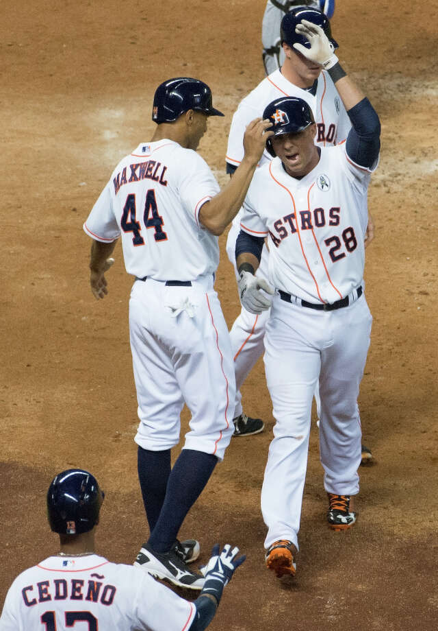 Rick Ankiel (28) celebrates with third baseman Matt Dominguez (30) and center fielder Justin Maxwell (44) after hitting a three-run home run. Photo: Smiley N. Pool, Houston Chronicle / © 2013  Smiley N. Pool