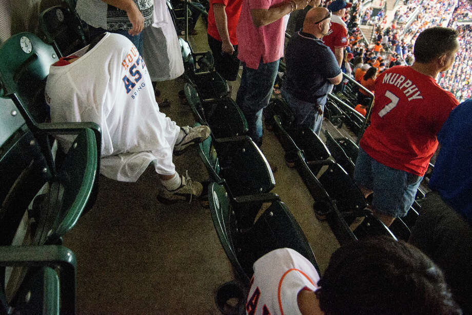 Donofrio Vasquez, 6, huddles under a give-away Houston Astros t-shirt as he sits with his family in the top row of the stadium. Photo: Smiley N. Pool, Houston Chronicle / © 2013  Smiley N. Pool