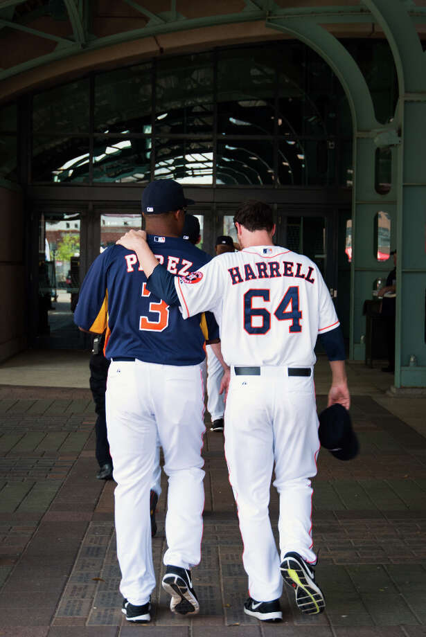 Astros starting pitcher Lucas Harrell puts his arm around bench coach Eduardo Perez as they walk into the stadium after appearing a fan pep rally. Photo: Smiley N. Pool, Houston Chronicle / © 2013  Smiley N. Pool