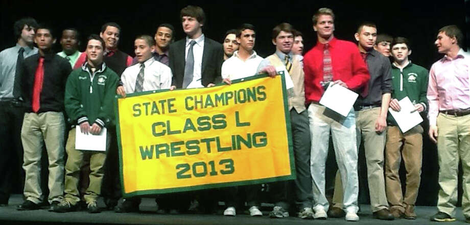 Athlets from the Green Wave wrestling team pose proudly with their state class 'L' championship banner during the March 27, 2013 winter sports awards ceremony at the school.  Courtesy of Liz Curtis Photo: Norm Cummings