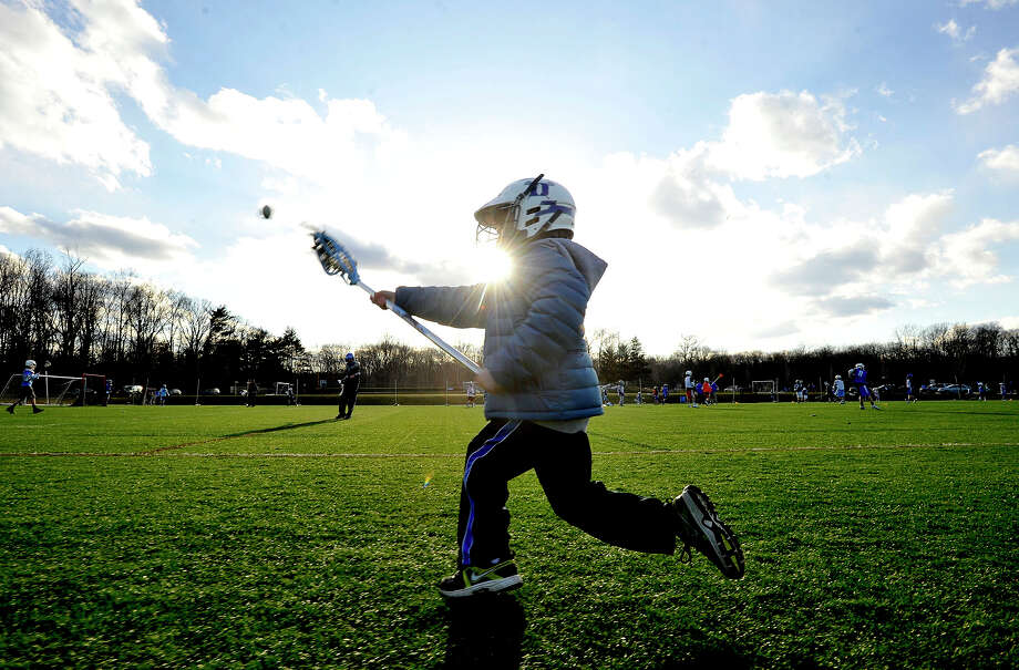 Seven-year-old Ryan Dahlquist tosses a ball around during youth lacrosse practice at Darien High School on Tuesday, April 2, 2013. Darien is considered to have the youngest average population among towns in southwestern Connecticut. People say one of the factors in raising children in Darien is the vibrant youth sports community. Photo: Jason Rearick / The (Stamford) Advocate