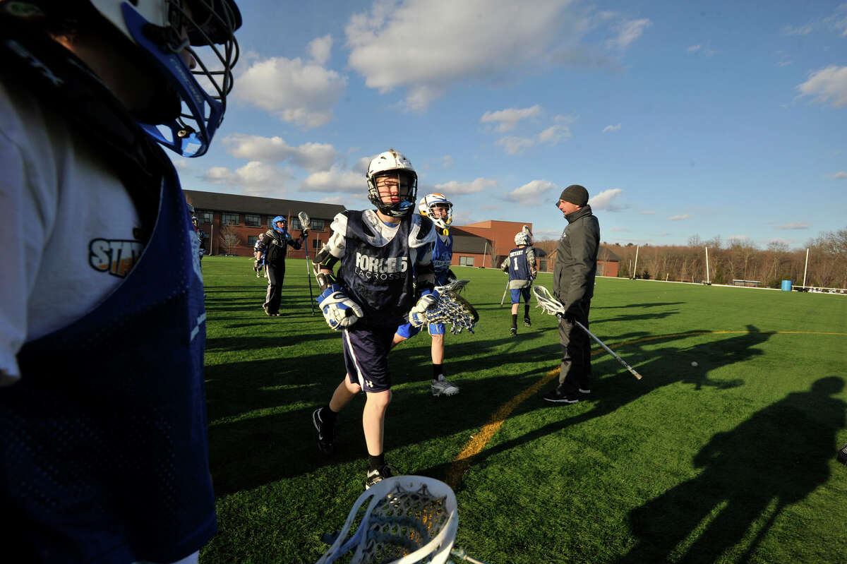 Youth lacrosse players run to their position during practice at Darien High School on Tuesday, April 2, 2013. Darien is considered to have the youngest average population among towns in southwestern Connecticut. People say one of the factors in raising children in Darien is the vibrant youth sports community.