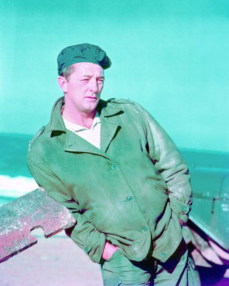 Robert Mitchum (1917-1997) wearing a green jacket and a dark blue beret, with his hands in the pockets of his trousers, leaning a length of rusted metal, circa 1960. Photo: Silver Screen Collection, Getty Images / 2011 Silver Screen Collection