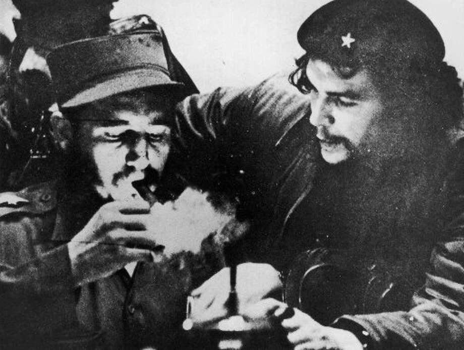Cuban revolutionary Fidel Castro (L) lights his cigar while Argentine revolutionary Che Guevara (1928-1967) looks on in the early days of their guerrilla campaign in the Sierra Maestra Mountains of Cuba, mid 1950s.