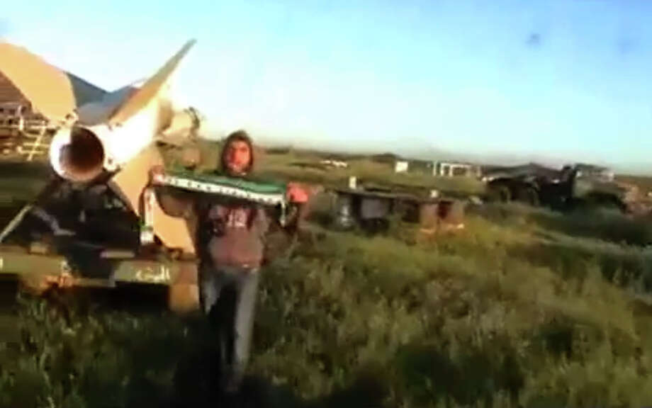 This image taken from video obtained from Ugarit News, which has been authenticated based on its contents and other AP reporting, shows a man holding a scarf in the colors of the Syrian revolutionary flag after rebels seized a military base in Daraa, Syria, on Wednesday, April 3, 2013. Syrian rebels captured a military base in the country's south on Wednesday after days of heavy fighting, activists said, in the latest advance by opposition fighters near the strategic border area with Jordan. (AP Photo/Ugarit News via AP video) Photo: Anonymous