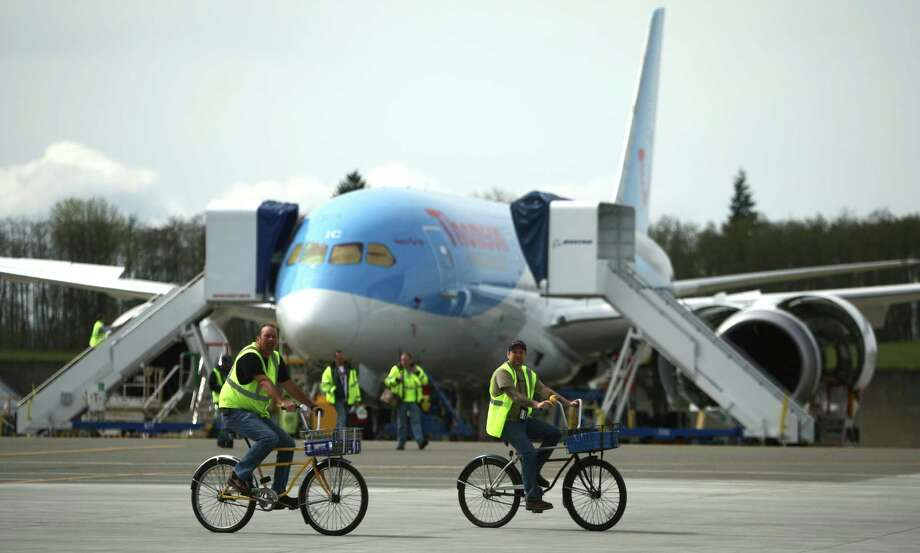 Boeing workers ride past on bicycles during a ceremony opening Boeing's new Everett Delivery Center. Photo: JOSHUA TRUJILLO / SEATTLEPI.COM