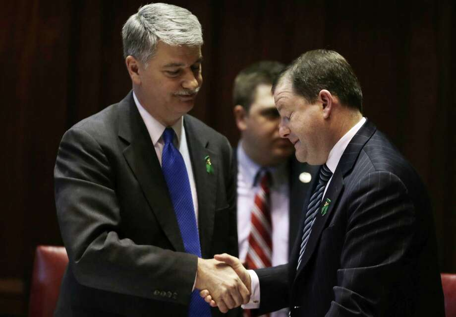 Senate Minority Leader John McKinney, R-Fairfield, who represents Newtown, Conn., right, and Senate President Donald Williams, D-Brooklyn, shake hands after the passage of a gun-control bill in the Senate chamber at the Capitol in Hartford, Conn., Wednesday, April 3, 2013. The bill passed the Senate and goes onto the Conn. Houses for approval. Hundreds of gun rights advocates are gathering at the statehouse in Hartford ahead of a vote in the General Assembly on proposed gun-control legislation. (AP Photo/Charles Krupa) Photo: Charles Krupa