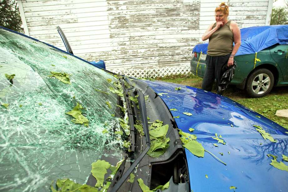 The path of late Tuesday's hailstorm could be traced Wednesday morning by the damage done to cars like Derinda Norred's. Photo: Brett Coomer, Staff / © 2013 Houston Chronicle