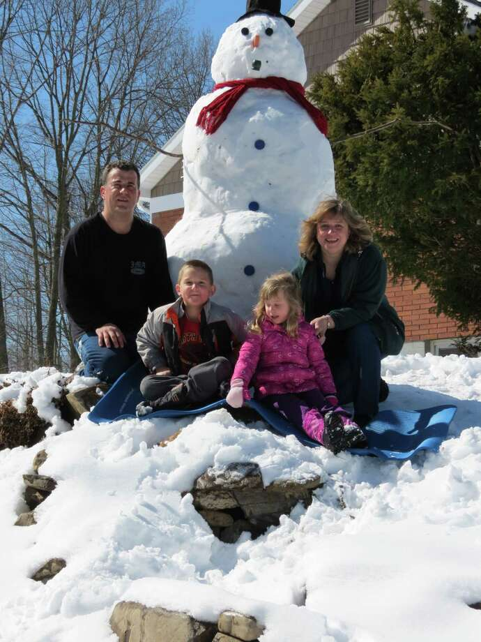 The last snowman created by the DeFelice family on Overlook Avenue in   Latham will soon be history as spring termperatures arrive. Here are Anthony, Kristen, Michael and Sara DeFelice (Pamela DeFelice)