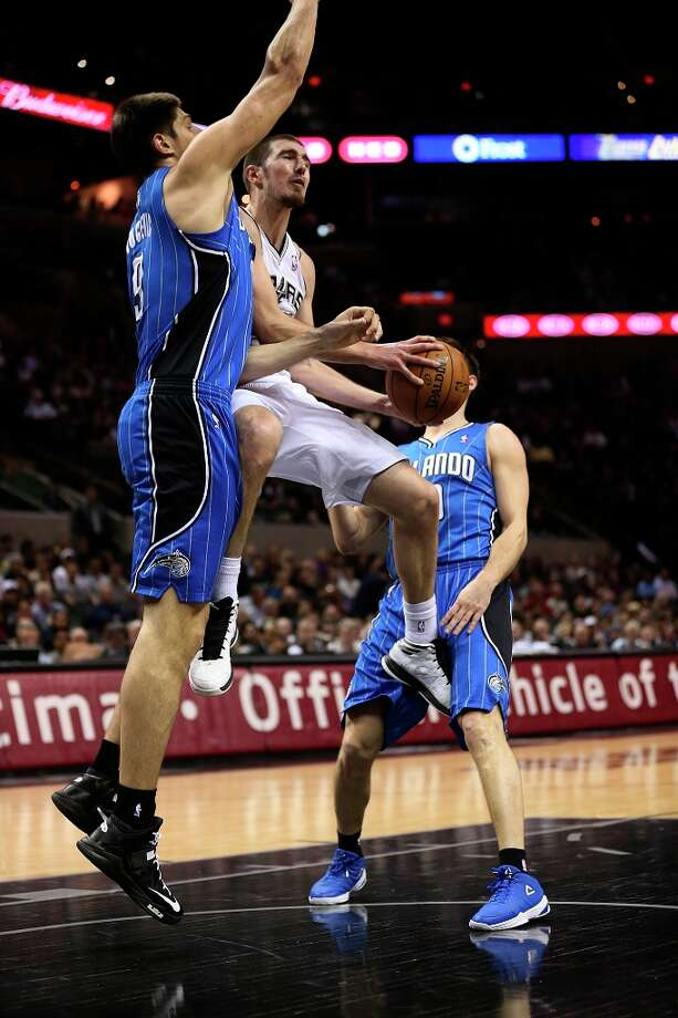 The Spurs\' Nando De Colo drives through Orlando Magic\'s Nikola Vucevic (left) and Beno Udrih during the first half at the AT&T Center, Wednesday, April 3, 3013. Photo: Jerry Lara, San Antonio Express-News / ©2013 San Antonio Express-News